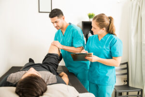 Physiotherapist Examining Customer's Leg While Colleague Noting In Clipboard